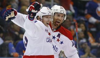 Washington Capitals center Nicklas Backstrom (19) of Sweden, left, celebrates with Capitals defenseman Brooks Orpik (44) after scoring the winning goal in overtime of Game 4 of a first-round NHL Stanley Cup hockey playoff series against the New York Islanders at Nassau Coliseum in Uniondale, N.Y., Tuesday, April 21, 2015.  The Capitals evened their series against the Islanders at 2-2. (AP Photo/Kathy Willens)