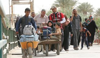 Displaced people from Ramadi cross the Bzebiz bridge heading towards Ramadi as they return to their homes, in Ramadi, 65 km west of Baghdad, Iraq, Tuesday, April 21, 2015. A United Nations humanitarian agency says more than 90,000 people have fled the Islamic State group's advance in Iraq's western Anbar province, which has set off fierce fighting in and around the provincial capital Ramadi. (AP Photo/Hadi Mizban)