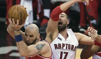 Washington Wizards center Marcin Gortat (4) battles for the ball against Toronto Raptors center Jonas Valanciunas (17) during the first half in Game 2 in the first round of the NBA basketball playoffs, Tuesday, April 21, 2015,  in Toronto. (Nathan Denette/The Canadian Press via AP)  MANDATORY CREDIT