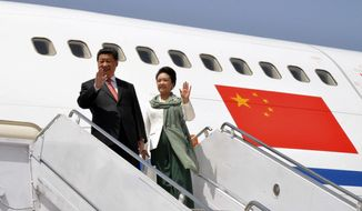 In this photo provided by Pakistan's Press Information Department, Chinese President Xi Jinping arrives with his wife Peng Liyuan at Nur Khan airbase in Islamabad, Pakistan, Monday, April 20, 2015. Xi arrived for a two-day visit during which the two sides will launch an ambitious $45 billion economic corridor linking Pakistan's port city of Gwadar with western China. (Press Information Department via AP) ** FILE **