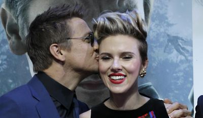 Jeremy Renner kisses Scarlett Johansson as they pose for photographers upon arrival at the premiere for the film 'The Avengers Age of Ultron' in London, Tuesday, 21 April, 2015. (Photo by Joel Ryan/Invision/AP)