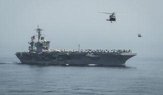 In this April 13, 2015 photo released by U.S. Navy Media Content Services, helicopters fly from the aircraft carrier USS Theodore Roosevelt during a vertical replenishment with the aircraft carrier USS Carl Vinson in the Gulf of Oman. The U.S. Navy has dispatched USS Theodore Roosevelt toward the waters off Yemen to join other American ships prepared to intercept any Iranian vessels carrying weapons to Houthi rebels, U.S. officials said on Monday. (Mass Communication Specialist 2nd Class Scott Fenaroli/ U.S. Navy Media Content Services via AP)
