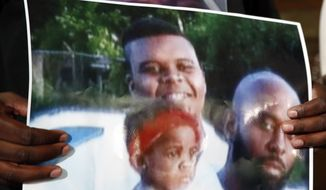 Michael Brown Sr., holds up a photo of himself, at right, his son, Michael Brown, top left, and a young child during a news conference Monday, Aug. 11, 2014, in Jennings, Mo. Michael Brown, 18, was shot and killed in a confrontation with police in the St. Louis suburb of Ferguson, Mo, on Saturday, Aug. 9, 2014.(AP Photo/Jeff Roberson)