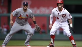 Washington Nationals' Bryce Harper, right, takes a lead off of first base while blowing a bubble as St. Louis Cardinals first baseman Matt Adams, left, looks on during the first inning of a baseball game, Thursday, April 23, 2015, in Washington. (AP Photo/Nick Wass)