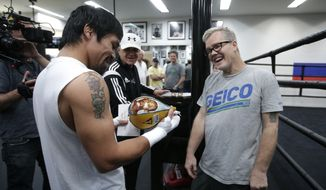 FILE - In this Monday, April 13, 2015, file photo, boxer Manny Pacquiao, left, of the Philippines, and his trainer Freddie Roach share a laugh as they look at a speed bag showing an images of Floyd Mayweather Jr., a gift from lawyer Robert Shapiro, background center, in Los Angeles. Roach has guided Pacquiao to the pinnacle of boxing, yet the most celebrated trainer of his era still rises before dawn and wins his daily fight with Parkinson's disease because he always finds new reasons to live.  (AP Photo/Jae C. Hong, File)
