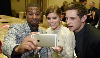 "Michael B. Jordan, left, Kate Mara, center, and Jamie Bell, cast members in the upcoming film ""Fantastic Four"" pose together for a selfie during the 2015 Pioneer of the Year dinner honoring 20th Century Fox Film Chairman and CEO Jim Gianopulos, during CinemaCon 2015 at Caesars Palace on Wednesday, April 22, 2015, in Las Vegas. (Photo by Chris Pizzello/Invision/AP)"