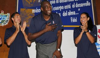 Former Los Angeles Lakers' Steve Nash, left, former NBA player Dikembe Mutombo, center, and former WNBA player Ticha Penicheiro acknowledge applause during the inauguration of the first NBA basketball training camp for Cuban players in Havana, Cuba, Thursday, April 23, 2015. Nash and Mutumbo were joined by ex-WNBA player Ticha Penicheiro and NBA coaches in teaching more than 100 Cuban basketball athletes, hoping to boost the game's popularity on the island. (AP Photo/Desmond Boyland)
