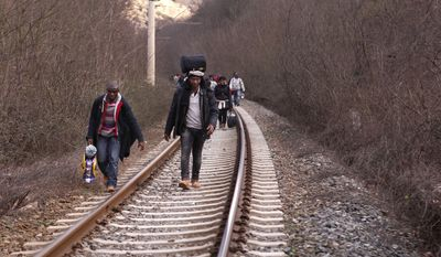 West African migrants walk on train tracks on their way toward the border with Macedonia near the town of Evzonoi, Greece, in this Saturday, Feb. 28, 2015, file photo. (AP Photo/Dalton Bennett)