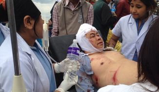 An Injured person receives treatment outside the Medicare Hospital in Kathmandu, Nepal, Saturday, April 25, 2015. A strong magnitude-7.9 earthquake shook Nepal's capital and the densely populated Kathmandu Valley before noon Saturday, causing extensive damage with toppled walls and collapsed buildings, officials said. (AP Photo/ Niranjan Shrestha)
