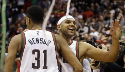 Milwaukee Bucks' John Henson and Jared Dudley celebrate after Game 4 of an NBA basketball first-round playoff series against the Chicago Bulls, Saturday, April 25, 2015, in Milwaukee. (AP Photo/Morry Gash)