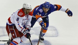 Washington Capitals left wing Alex Ovechkin (8) moves the puck up the ice against New York Islanders center Casey Cizikas (53) during the first period of Game 6 in the first round of the NHL hockey Stanley Cup playoffs, Saturday, April 25, 2015, in Uniondale, N.Y. (AP Photo/Julie Jacobson)