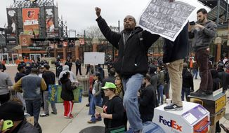A protestor stands on a mailbox outside of Oriole Park at Camden Yards before a baseball game between the Boston Red Sox and the Baltimore Orioles after a rally for Freddie Gray, Saturday, April 25, 2015, in Baltimore. Gray died from spinal injuries about a week after he was arrested and transported in a police van. (AP Photo/Patrick Semansky)