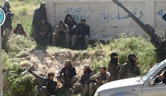 This image posted on the Twitter page of Syria's al-Qaida-linked Nusra Front on Saturday, April 25, 2015, which is consistent with AP reporting, shows Nusra Front fighters in the town of Jisr al-Shughour, Idlib province, Syria. Hard-line Syrian rebel groups entered the strategic town Saturday in northwestern Syria, sending government troops fleeing after intense clashes that have seen them take nearly all of a crucial province. Syria's civil war, now in its fifth year, has killed some 220,000 people, and wounded at least 1 million. (Al-Nusra Front Twitter page via AP)