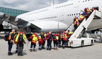 Members of a German rescue organization board a plane at the airport in Frankfurt, central Germany, Sunday, April 26, 2015, for their flight to earthquake-torn Nepal. International Search and Rescue Germany says a team of 52 relief workers including doctors, experts trained in searching for people buried under rubble and several dog squads will fly to Nepal. (Christoph Schmidt/dpa via AP)