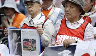 Survivors of the nuclear attacks on Japan in 1945 hold photographs during an anti-nuclear rally in Union Square in New York, Sunday, April 26, 2015. This year marks the 70th anniversary of the United States using nuclear bombs on Hiroshima and Nagasaki in Japan. (AP Photo/Seth Wenig) ** FILE **