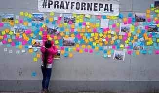 Nepali groups throughout the United States have come together in the earthquake's aftermath. Sophia Lama, 7, of New York, makes sure a message of hope holds onto a wall after on a growing memorial in Queens, New York. The America-Nepal Society serving the D.C. area has launched an initiative to get individuals and businesses to contribute to aid to Nepal. (Associated Press)