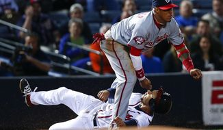 Atlanta Braves' Andrelton Simmons, bottom, is safe at third base as the ball gets away from Washington Nationals third baseman Yunel Escobar (5) in the fifth inning of a baseball game Monday, April 27, 2015, in Atlanta. Simmons was advancing to third from first base after a wild throw. Escobar was injured on the play and left the game. (AP Photo/John Bazemore)