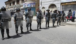 Afghan security forces stand guard during a protest demanding justice for a woman who was beaten to death by a mob after being falsely accused of burning a Quran more than one month ago, in downtown Kabul, Afghanistan, Monday, April 27, 2015. (AP Photo/Allauddin khan)