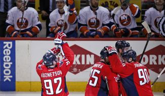 Washington Capitals center Evgeny Kuznetsov (92), from Russia, mimics a basketball shot in front of the New York Islanders bench after scoring the game winning goal during the third period of Game 7 in the first round of the NHL hockey Stanley Cup playoffs, Monday, April 27, 2015, in Washington. The Capitals won 2-1, to advance. (AP Photo/Alex Brandon)