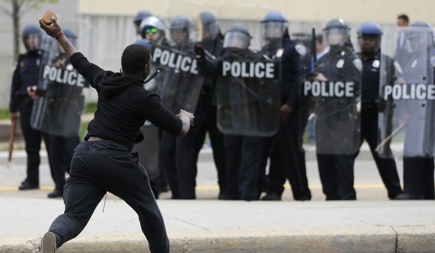 A man throws a brick at police Monday following the funeral of Freddie Gray in Baltimore. (Associated Press)