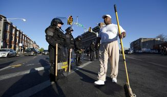 Victor Huntley-el thanks law enforcement officers as they stand guard, Tuesday, April 28, 2015, in Baltimore, in the aftermath of rioting following Monday's funeral for Freddie Gray, who died in police custody. (AP Photo/Matt Rourke)