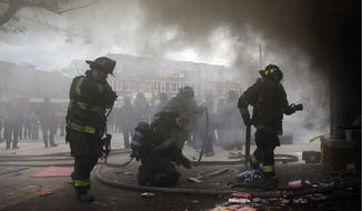 "Firefighters work to put out a fire at a store, Monday during unrest in Baltimore. ""The response has been a little slow but it's not the disaster that we saw in Ferguson,"" said David Harris, a police accountability expert with the University of Pittsburgh School of Law. (Associated Press)"