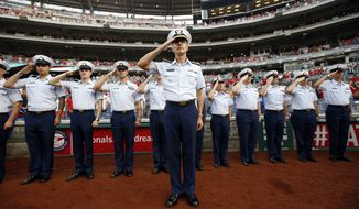 Vice Adm. Peter Neffenger, Vice Commandant of the U.S. Coast Guard, salutes in front of other members of the Coast Guard during the presentation of the colors before a baseball game between the Washington Nationals and the New York Mets at Nationals Park in Washington on Aug. 6, 2014. (Associated Press) **FILE**