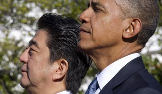 President Barack Obama listens to Japan's national anthem with Japanese Prime Minister Shinzo Abe during a state arrival ceremony, Tuesday, April 28, 2015, on the South Lawn of the White House in Washington. (AP Photo/Jacquelyn Martin)