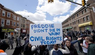 People gather Tuesday, April 28, 2015, in Baltimore, in the aftermath of rioting following Monday's funeral for Freddie Gray, who died in police custody. Gov. Larry Hogan said at a news conference Tuesday that Baltimore will not have a repeat of the riots that happened on Monday. (AP Photo/Matt Rourke)