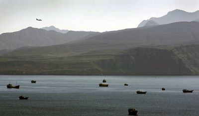 A plane flies over the mountains in south of the Strait of Hormuz as the trading dhows and ships are docked on the Persian Gulf waters near the town of Khasab, in Oman. (AP Photo/Kamran Jebreili, File)
