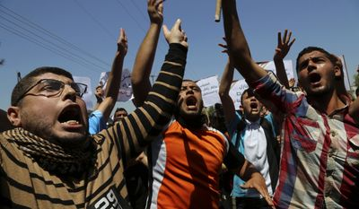 Palestinians chant slogans during a protest organized by the Palestinian Youth Organization, calling for an end to political division, reopening of the Rafah crossing border and the reconstruction of destroyed houses that were damaged in last summer's Israel-Hamas war, in Gaza City , in the northern Gaza Strip, Wednesday, April 29, 2015. (AP Photo/Adel Hana)