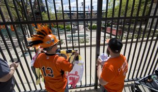 Fans Romeo Santos, left, and Matt Fouse gather ahead of a Baltimore Orioles baseball game against the Chicago White Sox's, Wednesday, April 29, 2015, outside Oriole Park at CamdenYards in Baltimore. The game was played in an empty Oriole Park at Camden Yards amid unrest in Baltimore over the death of Freddie Gray at the hands of police. (AP Photo/Matt Rourke)