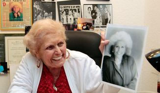 Jean Nidetch, founder of Weight Watchers, holds up a photo of herself at her home in Parkland, Fla., in this July, 18, 2011, file photo. (AP Photo/Alan Diaz, File)