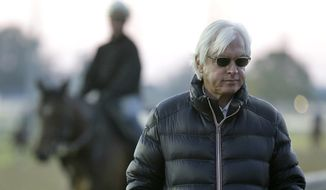 FILE - In this April 28, 2015 file photo, trainer Bob Baffert watches horses workout at Churchill Downs, in Louisville, Ky. Before Baffert won the Kentucky Derby for the first time, he lost.  Seize the moment is Baffert's mantra. Don't think about those glorious wins by Silver Charm in '97, Real Quiet in '98 and War Emblem in '02. And for sure, don't even mention the losses. Three of them with favorites, one by a nose, and another with the horse he calls the best he's ever trained. Of course, that tune could change by Saturday night. (AP Photo/Charlie Riedel, File)