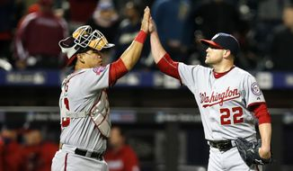 Washington Nationals catcher Wilkson Ramos (40) celebrates with Nationals relief pitcher Drew Storen (22) after Storen closed out the Nationals 8-2 victory over the New York Mets in a baseball game in New York, Thursday, April 30, 2015. (AP Photo/Kathy Willens)