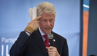 "Former President Bill Clinton gestures while wearing a bracelet given to him by the pupils, as he and Chelsea Clinton talk about their foundation's ""No Ceilings"" project about the participation of women and girls globally, at the Farasi Lane Primary School in Nairobi, Kenya Friday, May 1, 2015. Former President Bill Clinton and daughter Chelsea Clinton are in the East African nation of Kenya as part of a wider tour of projects run by the family's Clinton Foundation. (AP Photo/Ben Curtis)"