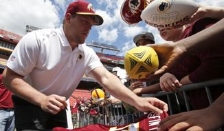 Washington Redskins draft pick offensive lineman Brandon Scherff, left, returns a jersey after signing it during an NFL football draft day fan fest Saturday, May 2, 2015, in Landover, Md. (AP Photo/Alex Brandon)