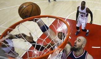 Washington Wizards center Marcin Gortat, right,  goes up for a basket against  Atlanta Hawks forward DeMarre Carroll  in the second half of an NBA second-round basketball payoff series game Sunday, May 3, 2015, in Atlanta. Washington won 104-98. (AP Photo/John Bazemore)