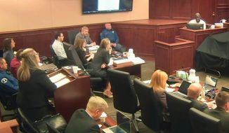 In this image taken from Colorado Judicial Department video, Colorado theater shooter James Holmes, left rear in light-colored shirt, watches during testimony by witness Derick Spruel, upper right, on the second day of his trial in Centennial, Colo., Monday, April 27, 2015. (Colorado Judicial Department via AP, Pool, File)