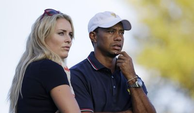 This Oct. 3, 2013, file photo shows Tiger Woods watching with his girlfriend Lindsey Vonn at the Presidents Cup golf tournament at Muirfield Village Golf Club in Dublin, Ohio. Vonn announced on Sunday, May 3, 2015, that she and Woods have decided to end their three-year relationship. (AP Photo/Darron Cummings, file)