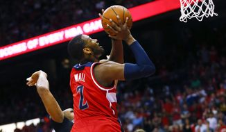 Washington Wizards guard John Wall (2) goes up for a shot against Atlanta Hawks Al Horford, left, and Kyle Korver in the second half of an NBA second-round basketball payoff series game, Sunday, May 3, 2015, in Atlanta. Washington won 104-98. (AP Photo/John Bazemore)