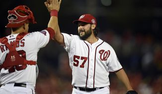 Washington Nationals relief pitcher Tanner Roark (57) celebrates a 6-4 win over the Miami Marlins with catcher Wilson Ramos (40) in a baseball game Monday, May 4, 2015, in Washington. (AP Photo/Nick Wass)