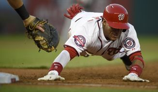 Washington Nationals' Yunel Escobar dives back to first as he was safe on a single during the third inning of a baseball game against the Miami Marlins, Monday, May 4, 2015, in Washington. (AP Photo/Nick Wass)