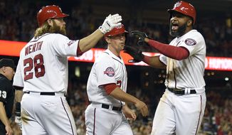 Washington Nationals center fielder Denard Span, right, reacts with Jayson Werth (28) after Span and Tyler Moore, center, scored on a single by Yunel Escobar during the eighth inning of a baseball game against the Miami Marlins, Monday, May 4, 2015, in Washington. The Nationals won 6-4. (AP Photo/Nick Wass)