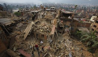 FILE - In this Sunday, April 26, 2015, file photo, rescue workers remove debris as they search for victims of an earthquake in Bhaktapur near Kathmandu, Nepal. A strong magnitude earthquake shook Nepal's capital and the densely populated Kathmandu Valley before noon Saturday, causing extensive damage with toppled walls and collapsed buildings, officials said. (AP Photo/Niranjan Shrestha, File)