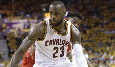 Cleveland Cavaliers forward LeBron James (23) drives around Chicago Bulls guard Jimmy Butler during the first half of Game 1 in a second-round NBA basketball playoff series Monday, May 4, 2015, in Cleveland. (AP Photo/Tony Dejak)