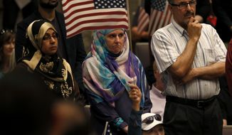 In this April 2, 2015 photo, Aminah Hamed, center, and Sami Hamed stand while a resident speaks against Texas House Bill 562, a statehouse bill widely believed to target Islamic influence in America, while Sherry Mecom waves an American flag from her seat during an Irving city council meeting in Irvin, Texas. Gunmen attacking at a contest for Muslim Prophet Muhammed cartoons May 3, 2015, in Garland, Texas, came as Muslims in Texas were already feeling aggrieved and fearful as anti-Islam sentiment over the last several months has reverberated from the state Capitol to local governments. (Rose Baca/The Dallas Morning News via AP)