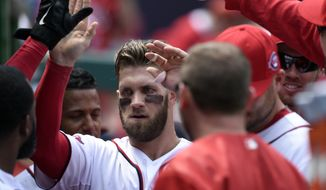Washington Nationals right fielder Bryce Harper, center, is congratulated by his teammates after hitting a home run against the Miami Marlins during the third inning of their baseball game at Nationals Park in Washington, Wednesday, May 6, 2015. This was Harper's second home run of the game.(AP Photo/Susan Walsh)
