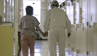 FILE - In this Wednesday, April 9, 2008 file photo, Debbie Coluter, a certified nursing assistant, holds the hand of an elderly inmate with Alzheimer's disease, as she helps him to his cell at the California Medical Facility in Vacaville, Calif. (AP Photo/Rich Pedroncelli) **FILE**