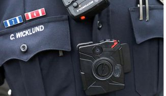 In this Nov. 5, 2014, file photo, Sgt. Chris Wicklund of the Burnsville, Minn., Police Department wears a body camera beneath his microphone. Cleveland's move to buy 1,500 police body cameras and data storage could cost up to $3.3 million over five years, a higher price tag than previously known and an illustration of the long-term costs of such programs with Taser International. (AP Photo/Jim Mone, File)